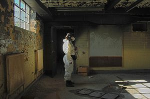 Image showing person in protective suit in a rundown building