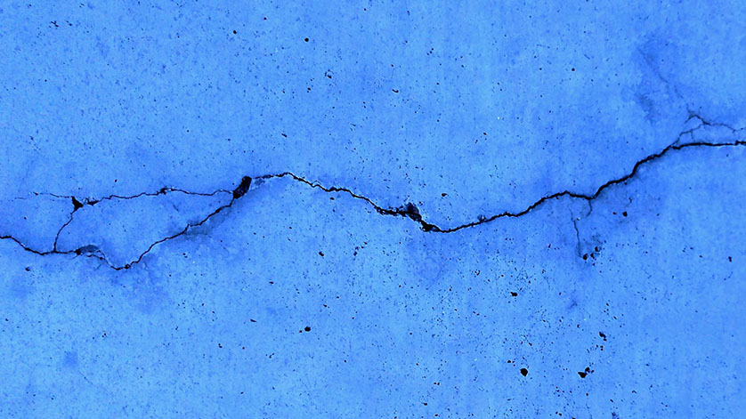 A blue wall with crack running through it