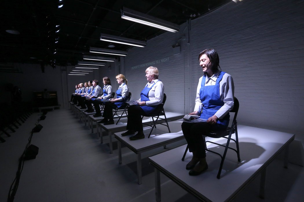 A performance photo of women on chairs