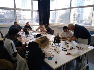 A room with 8 people working at a table covered in wires