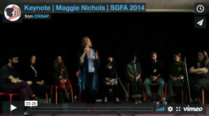 "A vimeo video still showing a woman speaking into a microphone and 8 people seated behind her. The text reads ""Keynote 