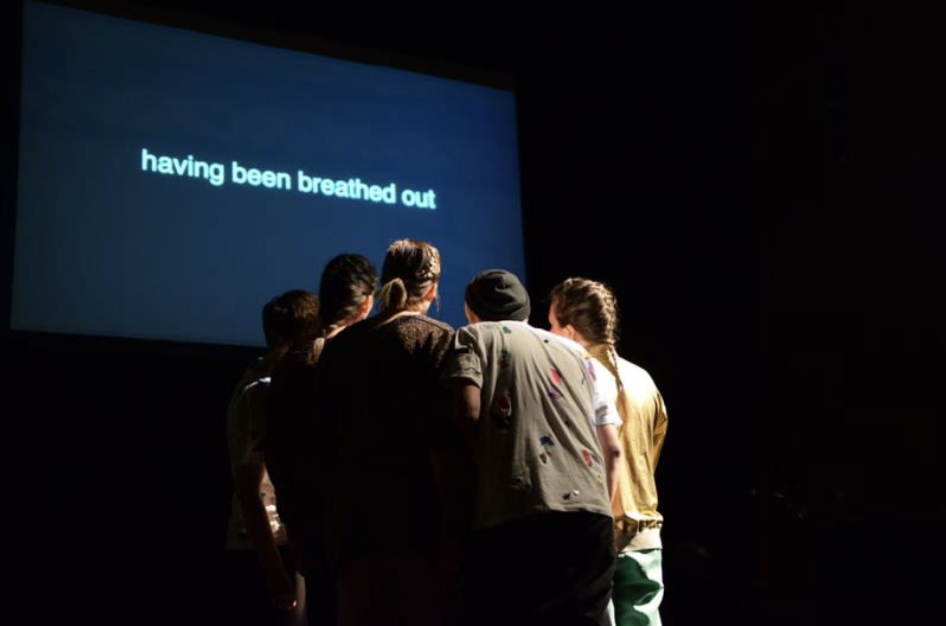 "A group of peoples huddles inwards, standing infront of a screen with pale blue text on a dark blue background that reads ""having been breathed out"""