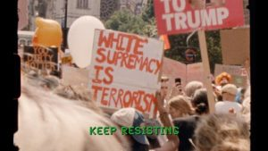 "a crown with plackards that read ""white supremacy is terrorism"" with green subtitle text that reads ""keep resisting"""