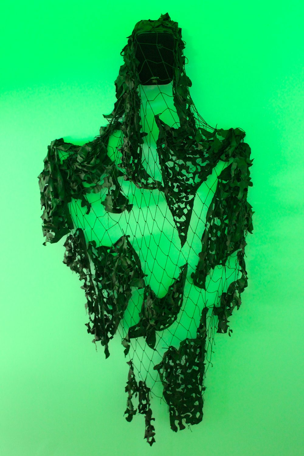 A camouflage net handing over a speaker on a bright green wall