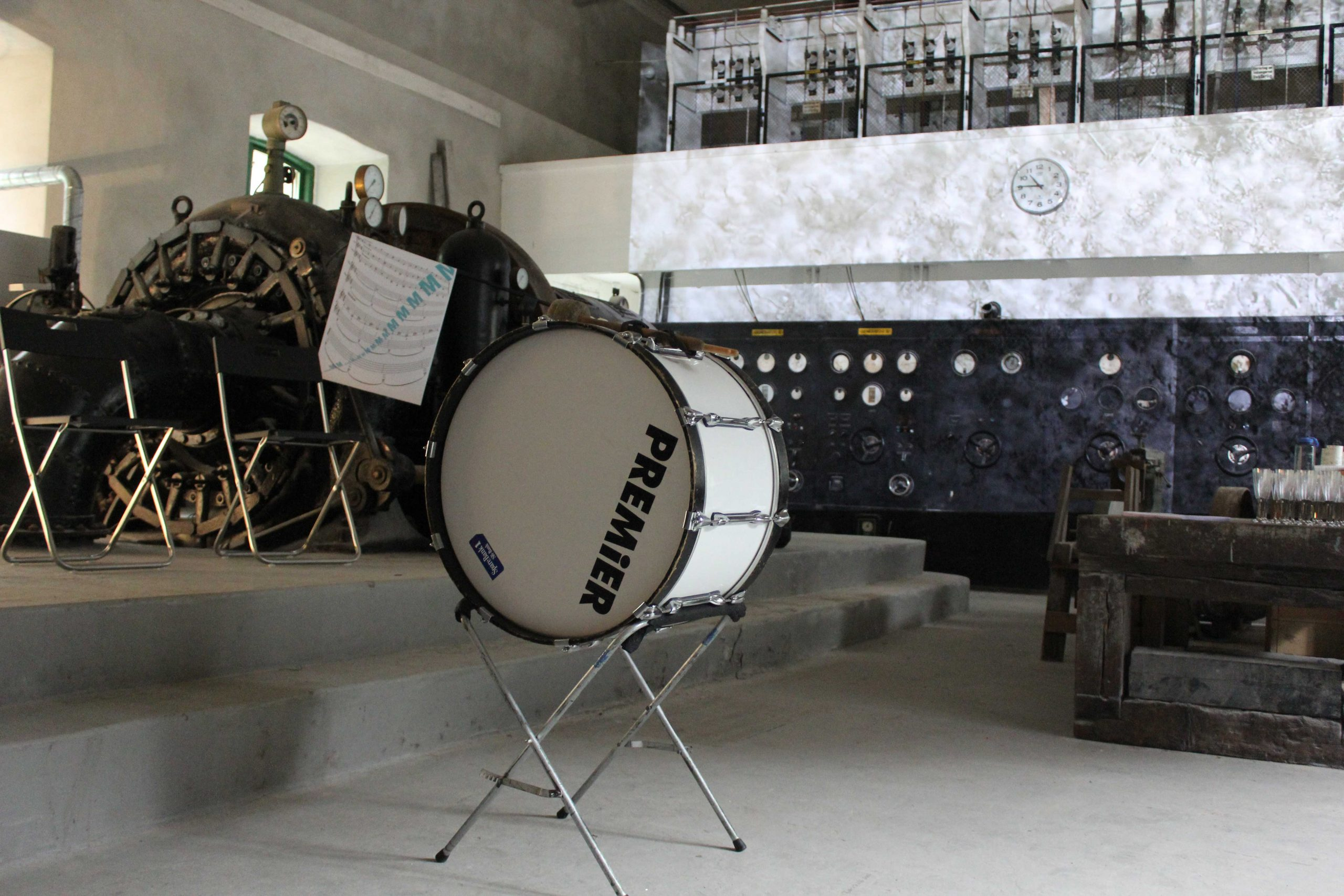 a bass drum on a stand in a room with a projection and equipment in the background