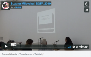 "a vimeo still of a video showing a woman talking into a microphone by a projection. Text reads ""Suzana Milveska 